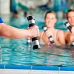 A couple performing aqua aerobics in a pool.