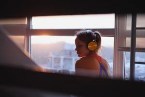 Young Woman Listening To Music With Wireless Earphones