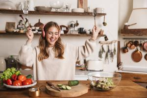 Image of smiling woman using headphones and dancing while cooking
