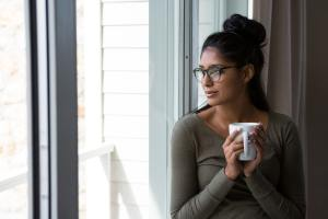 Woman with coffee cup by window
