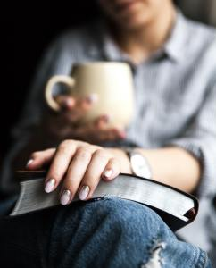 Young woman reading a book and holding cup of tea or coffee
