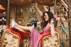 Cheerful lady in sunglasses and dress holding lolly pop candy riding on carousel in amusement park