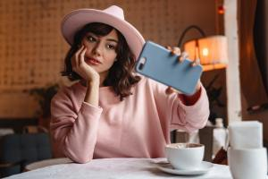 Woman indoors in cafe using mobile phone take a selfie.