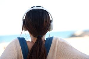 Woman sitting by beach with headphones