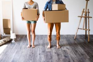 Unrecognizable couple with boxes moving in new house.