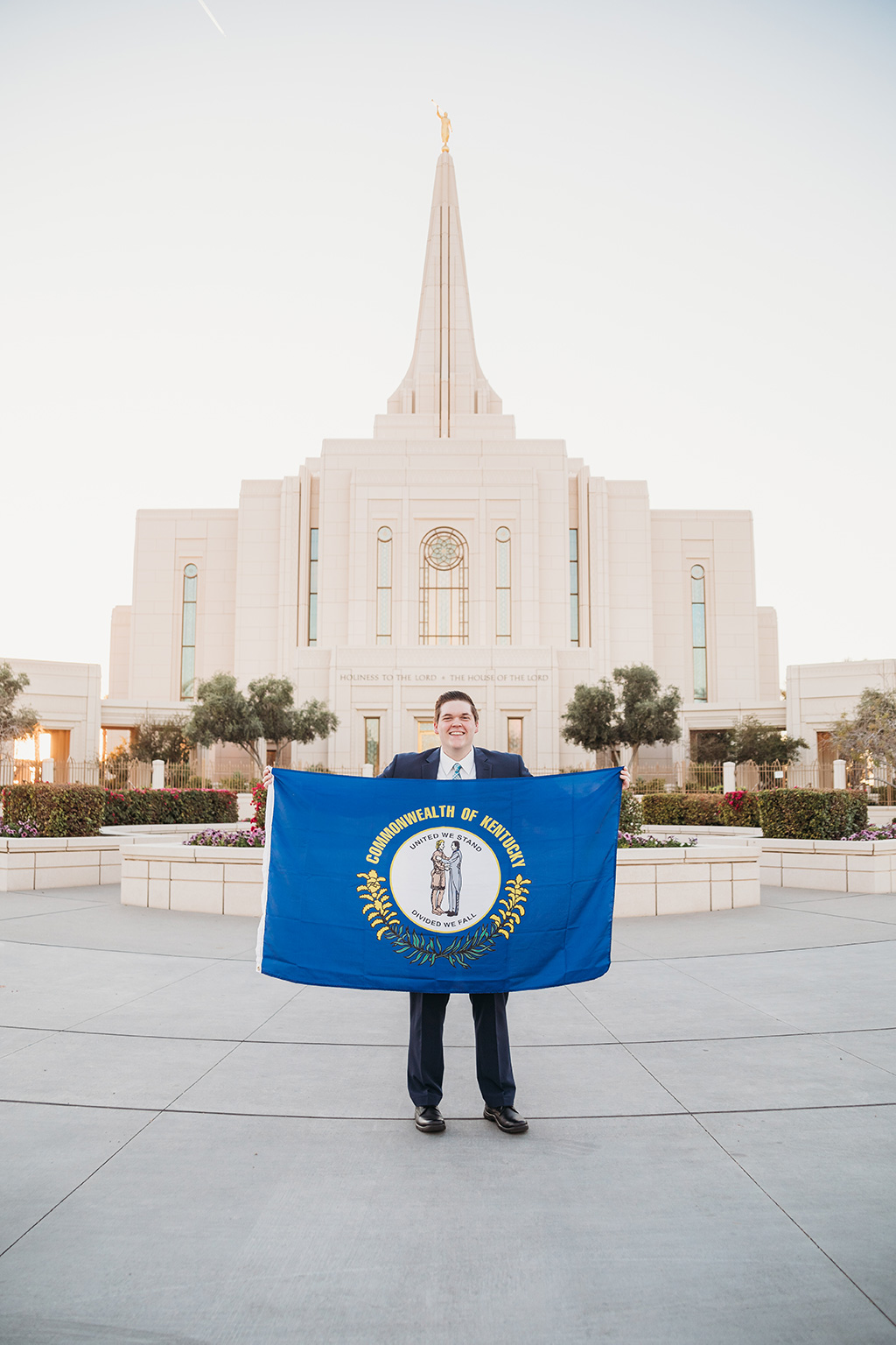 LDS missionary photoshoot in front of the gilbert arizona temple holding kentucky flag