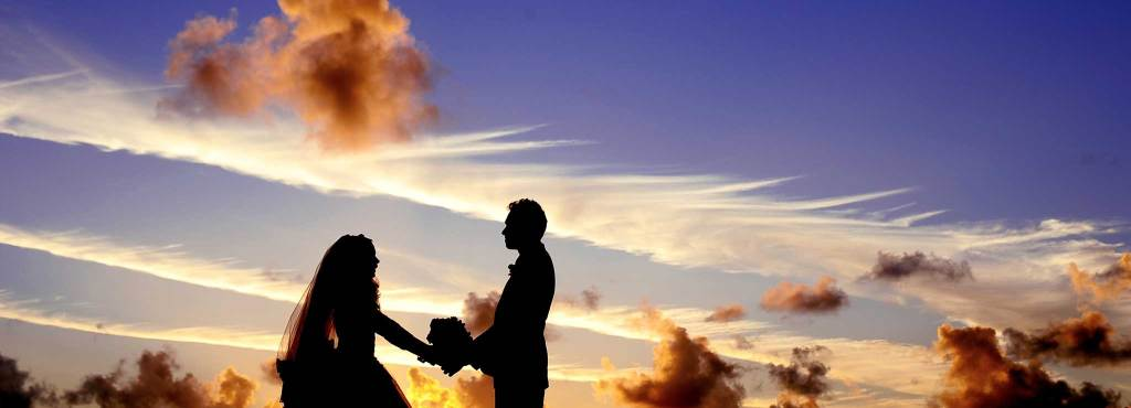 A couple marrying in front of a beautiful sky