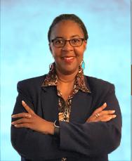 Larcenia L. Freeman smiling with arms folded.