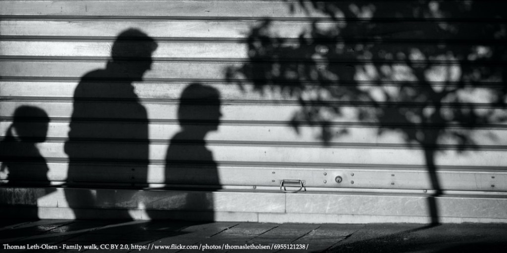 Shadow on the wall with a family of three people representing current economics of childbearing