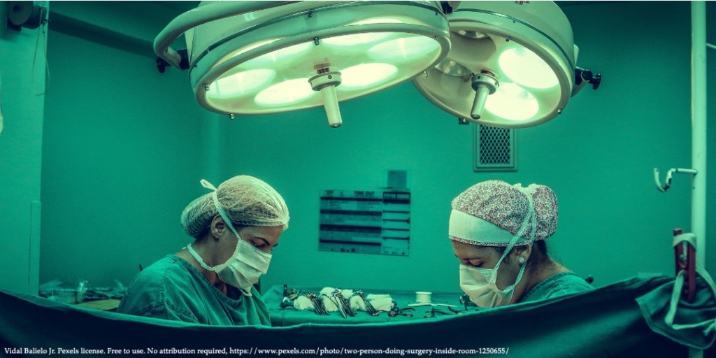 An image of surgery room with two doctors in green protection gear representing public healthcare expenditures