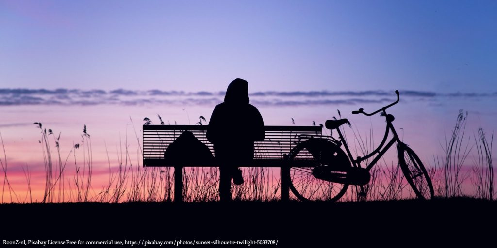 Image of a woman sitting alone in the sunset representing dimensions of well-being
