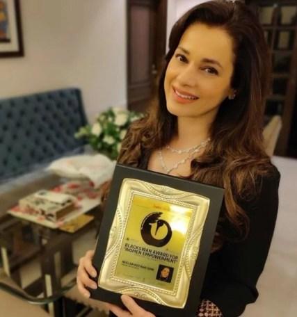Neelam Kothari posing with her award