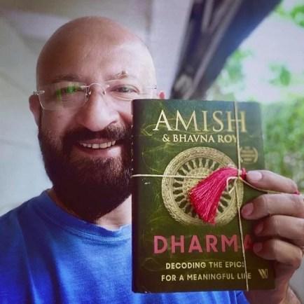 Raj Kaushal holding a book by Amish