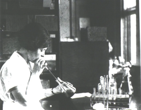 Vintage black-and-white photo of a scientist pipetting with their mouth