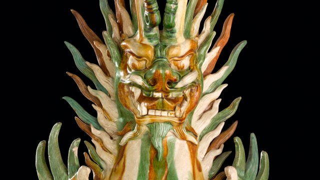 Fearsome composite creature with horns and fangs, glazed with green, orange, and white.