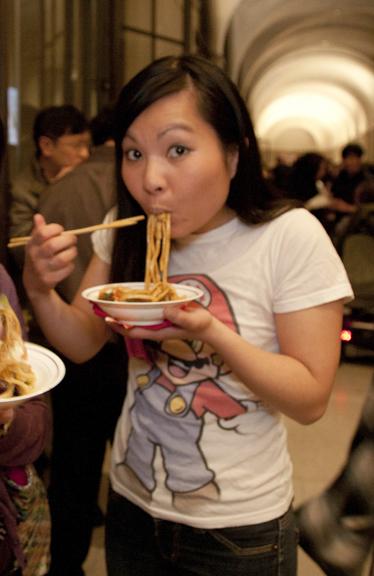 Woman slurping noodles out of a bowl.