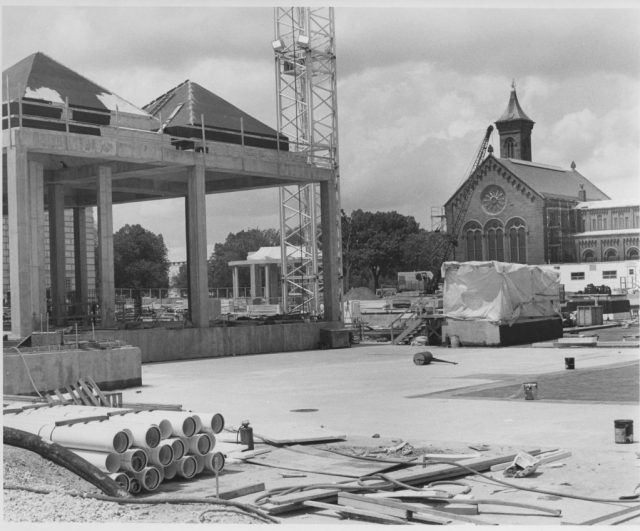 Black and white image of construction site of Sackler on left with only the roof and pillars.