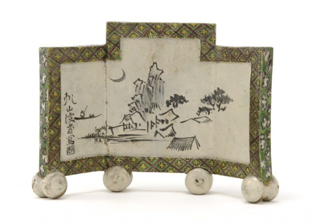 Small 3-fold screen with house on mountain painted in center - edges covered with diamond patterned frame.