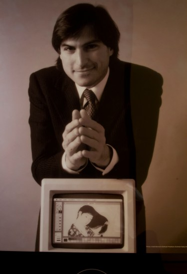 Young Steve Jobs in a suit and tie leans forward with hands folded, on a small Apple monitor which displays a digital rendering of the Goyo print in MacPaint.