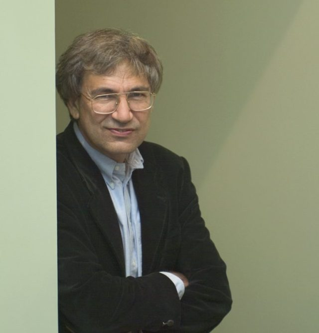Orhan Pamuk, arms folded in front, standing in front of a green wal.l