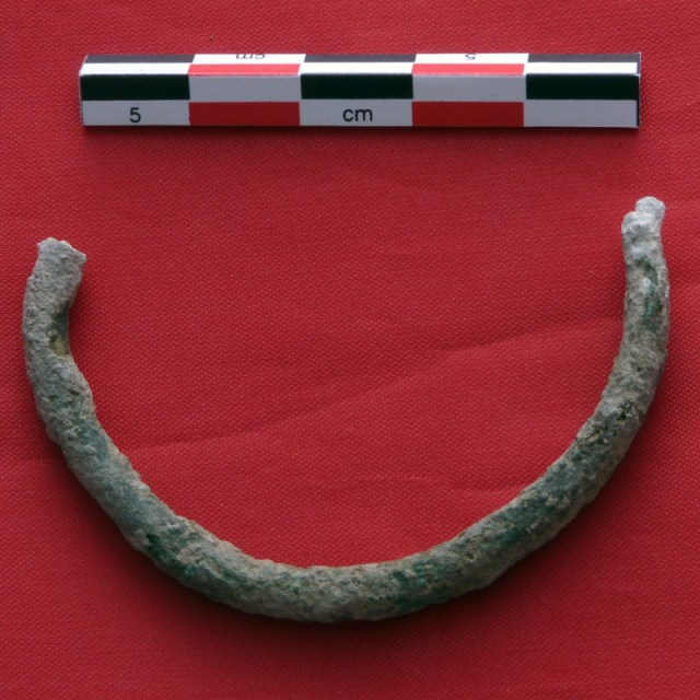 Half of a broken bronze bracelet, covered in green and white patina, next to an archaeological centimeter scale, on a red surface.