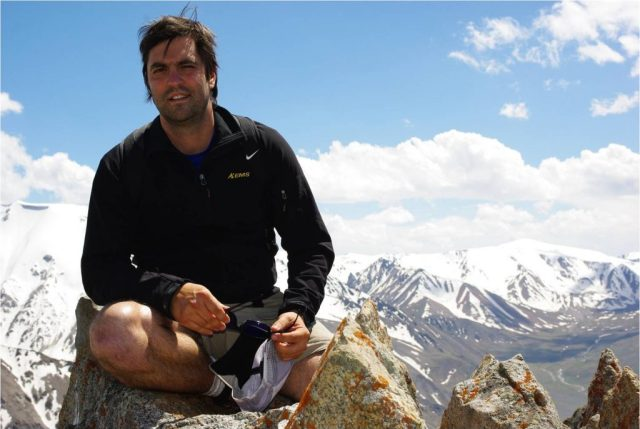 Man sitting on top of a mountain with mountains in background.