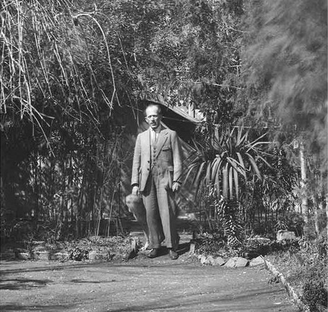 Ernst Herzfeld surrounded by plants.