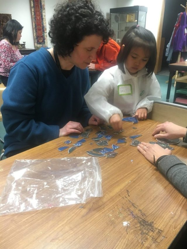 "Conservator Ellen Chase works with program participants on reassembling their ""ceramic"" puzzles during the first Art and Me workshop."