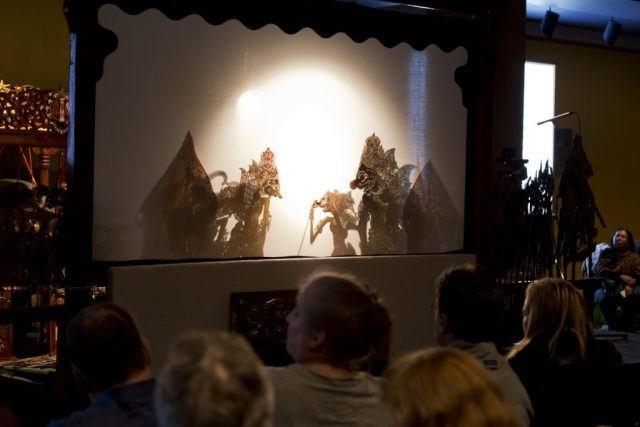 Crowd watches a shadow puppet show.
