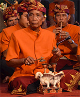 Indonesian musicians in bright orange costumes.