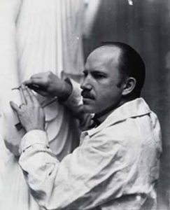 Artist Paul Manship working on the arm of a marble sculpture.