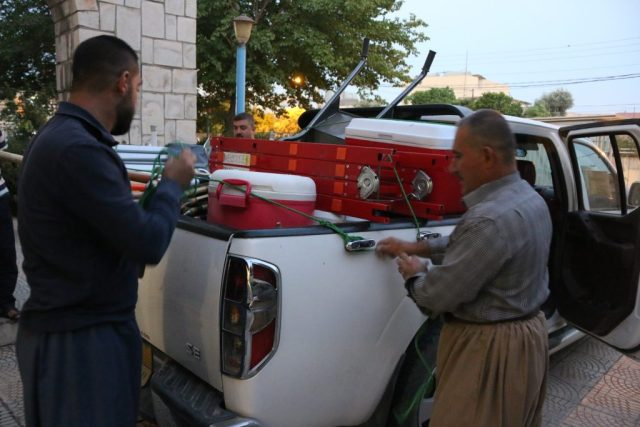 Two men loading supplies into back of truck.