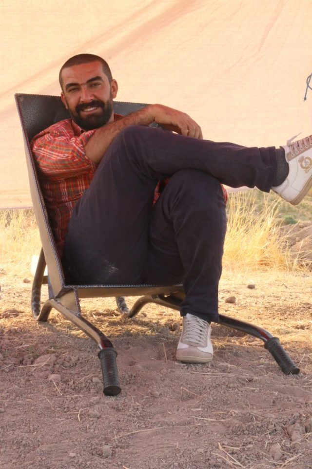 man sitting under tarp in chair on the ground.