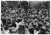 Black and white photograph of a crowd of people, many of which are wearing hats with the same print.