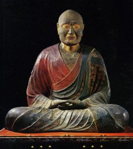 Sculpture of a monk, with some red and dark coloring