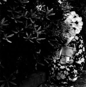 black and photo of person holding a cup, wearing a kimono. The individual's face is obscured by a large flowering bush in the foreground of the image