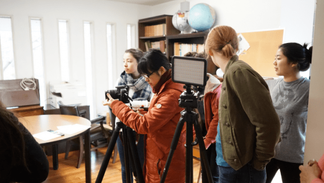Yingzhi stands behind the camera as the director of photography.