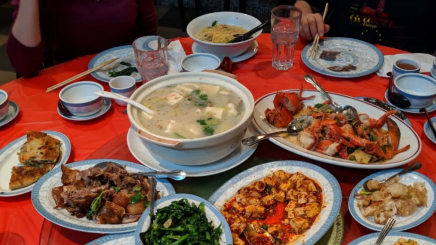many chinese dishes on a red tablecloth