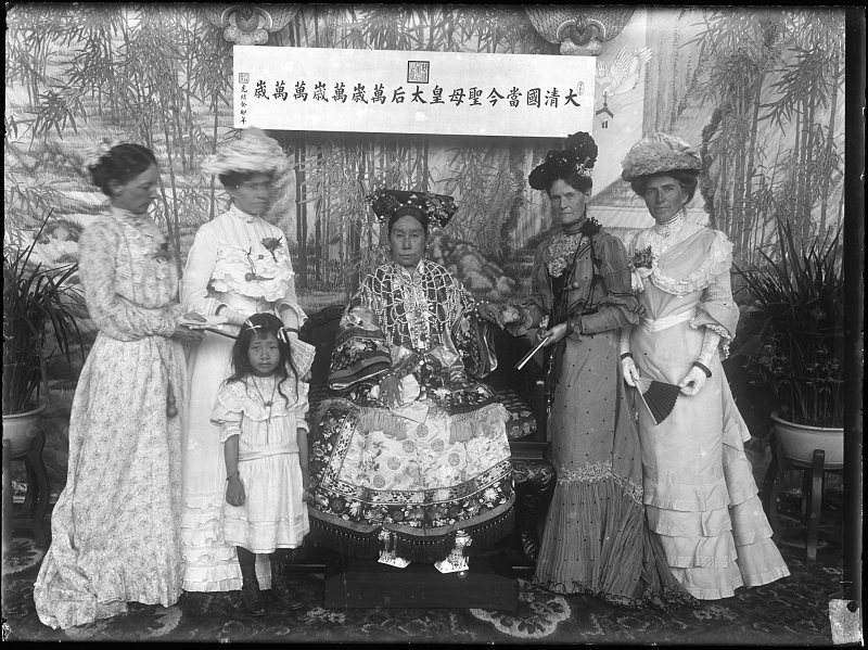 black and white photograph of the Empress Dowager Cixi seated in the center surrounded by four women and a little girl