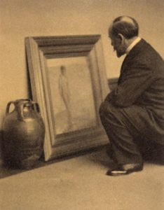 Man looks at framed painting in a squatting position