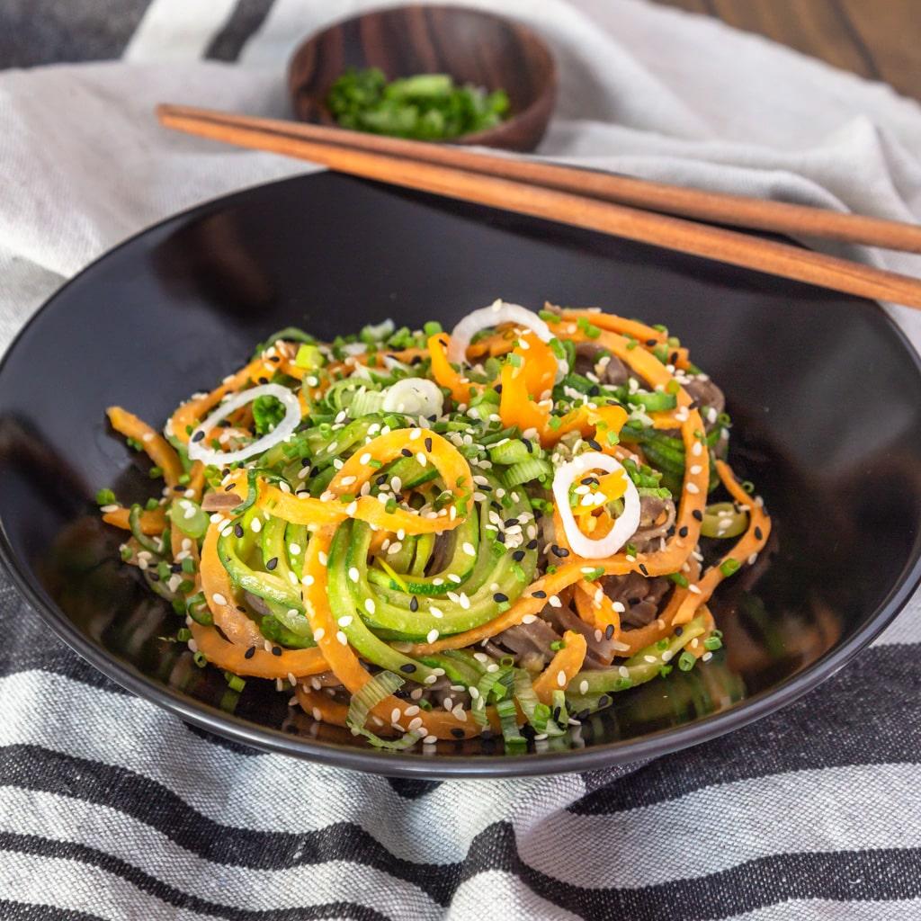 Un wok de nouilles de légumes sautées, avec une sauce gingembre, cacahuète et citron vert ! Recette vegan et adaptable sans gluten.