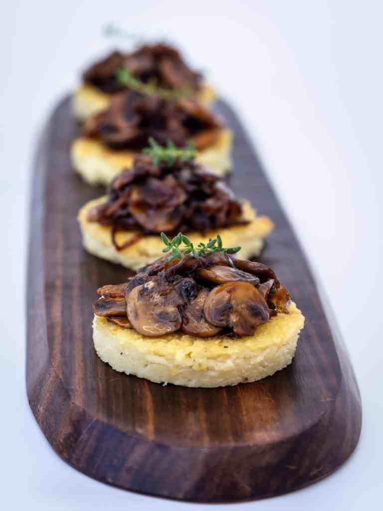 Une recette de petites bouchées de polenta et de champignons et oignons caramélisés. Une recette végétarienne, sans gluten et même végétalienne pour l'apéritif ! Idéale pour la saison des fêtes de fin d'année.