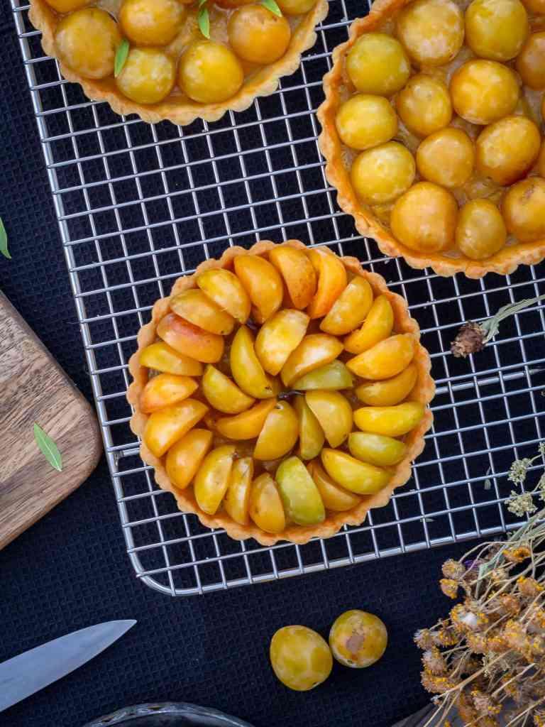 De jolies tartelettes aux mirabelles composée d'une pâte sablée vanillée, recouverte d'un crème d'amande où se logent de petits morceaux de mirabelles crues, puis d'une compotée de mirabelles infusée à la verveine citronnée, le tout couronné par un dégradé de mirabelles arrangées avec amour !