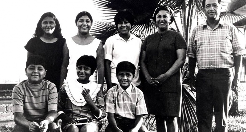 "Helen and Cesar Chavez with six of their eight children in 1969 at the United Farm Workers' ""Forty Acres"" property outside Delano. Standing from left are Anna, Eloise and Sylvia. Seated from left are Paul, Elizabeth and Anthony. (United Farm Workers)"