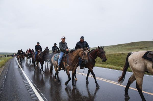Each morning at the Cannon Ball prayer camps, participants walk and ride horse from the campsite to the construction site, about a half-mile away. Songs are sung and prayers are offered by all. (Photo: Thosh Collins)