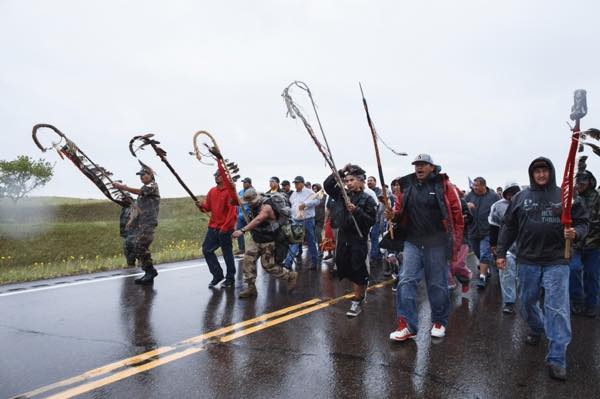 Veterans from tribal nations, including several bands of Lakota and Ojibwe people, carry staffs to lead the crowd toward the pipe ceremony just outside the gate of the construction site. (Photo: Thosh Collins)