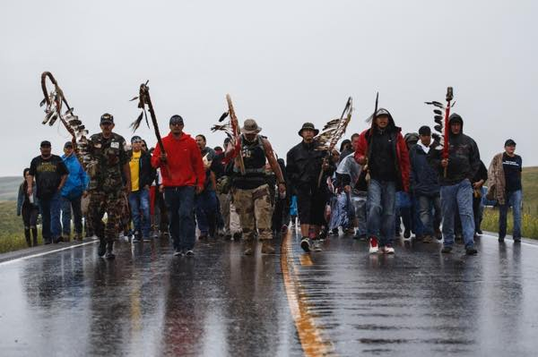 "The Lakota people refer to warriors as ""akicita"" and still use this term while referring to veterans. The akicita lead the way toward the prayer site in the rain. (Photo: Thosh Collins)"