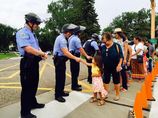 Young Rita Waln led a procession of women and children who shook hands with officers at the ND Capitol after they held a demonstration to deny charges that weapons or pipe bombs were at the Lakota encampments along the Missouri River. About 200 water protectors took their message of peace to the governor that they are unarmed and peaceful.