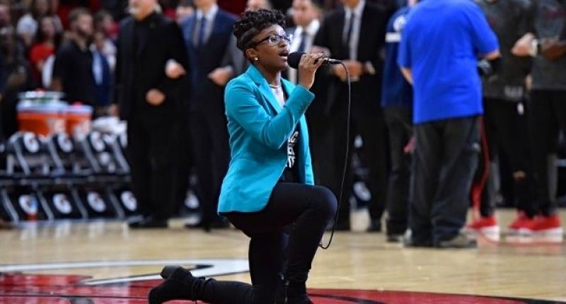 Oct 21, 2016; Miami, FL, USA; National Anthem singer Denasia Lawrence kneels as she sings the anthem prior to the game between the Miami Heat and the Philadelphia 76ers at American Airlines Arena. Mandatory Credit: Jasen Vinlove-USA TODAY Sports.