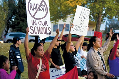 "photo by Derek Brouwer. Demonstrators rallied outside the Polson High School homecoming football game and chanted ""No more hate!"" to protest a racist display at the school the previous day."